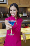Woman Holding Out Blue Martini Stock Photography