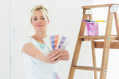 Woman holding out color swatches in new house Stock Photo