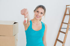 Woman holding out with key besides boxes in new house Royalty Free Stock Photos