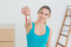 Woman holding out with key besides boxes in new house Royalty Free Stock Images