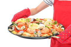 Delicious paella in pan. Woman holding a paella in pan stock photo