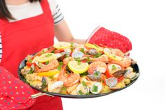 Delicious paella in pan. Woman holding a paella in pan royalty free stock photography