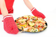 Delicious paella in pan. Woman holding a paella in pan royalty free stock image