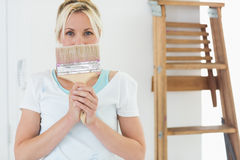 Woman holding paint brush in front of face at the new house Royalty Free Stock Photo
