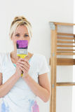 Woman holding paint brush in front of face at new house Royalty Free Stock Image