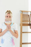 Woman holding paint brush in front of her face at new house Stock Photo