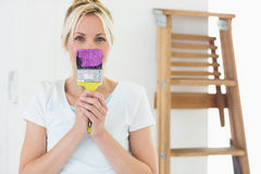 Woman holding paint brush in front of her face at new house Stock Photography