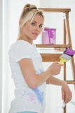 Woman holding paint brush in front of ladder at new house Royalty Free Stock Photo