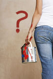 Woman Holding Paint Can With Painted Question Mark On Wall. Rear view midsection of a woman holding paint can with painted question mark on wall Royalty Free Stock Photography