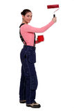 Woman holding paint roller Stock Photos