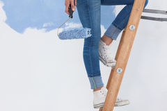 Woman holding paint roller on ladder Stock Photos