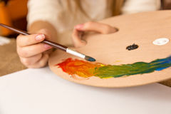 Woman holding paintbrush and choosing paint on pallet Royalty Free Stock Photography