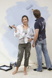 Woman Holding Paintbrush While Man Painting Wall Stock Images