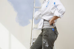Woman Holding Paintbrush By Stepladder Against Unpainted Wall Royalty Free Stock Image