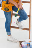 Woman holding paintbrush and wearing tool belt Royalty Free Stock Photos