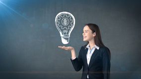 Woman holding painted glowing light with business words and terms on the open hand palm, drawn background. Concept. Royalty Free Stock Photos