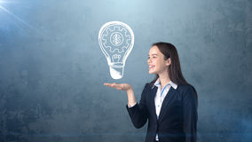 Woman holding painted glowing light with business words and terms on the open hand palm, drawn background. Concept. Royalty Free Stock Images
