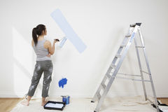 Woman Holding Paintroller While Analyzing Paint On Wall. Full length rear view of young woman holding paintroller while analyzing paint on wall Stock Photography