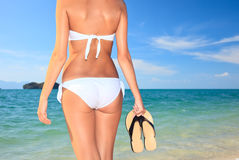 Woman holding a pair of flip flops in the water Stock Photography
