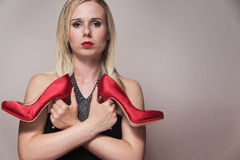 Woman holding a pair of red shoes Stock Photography