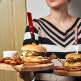 Woman holding pair of round wooden trays with burgers Stock Photo