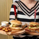 Woman holding pair of round wooden trays with burgers Royalty Free Stock Image