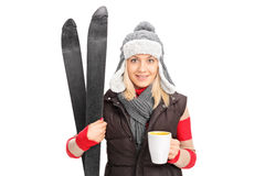 Woman holding a pair of skis and drinking hot tea Royalty Free Stock Image