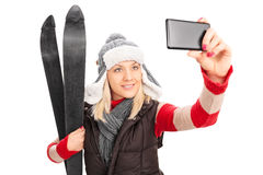 Woman holding a pair of skis and taking selfie Royalty Free Stock Images