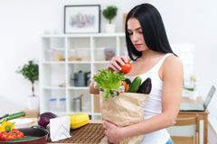 Woman holding paper bag with fresh grocery looking down attentively, choosing ingredients for diet healthy meal. Woman holding paper bag with fresh grocery Stock Images