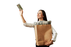 Woman holding paper bag with money. Smiley woman holding paper bag with money. isolated on white background royalty free stock photography