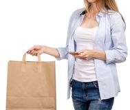 Woman holding a paper bag smartphone mobile phone shopping beauty. On a white background. Isolation stock photos