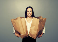 Woman holding paper bags over dark. Glad woman holding paper bags over dark background Royalty Free Stock Photography