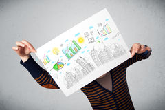 Woman holding a paper with charts and cityscape in front of her Stock Photo