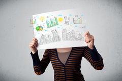 Woman holding a paper with charts and cityscape in front of her Stock Photos