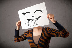 Woman holding a paper with cute smiley face on it in front of he Stock Image