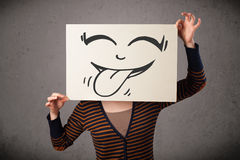 Woman holding a paper with cute smiley face on it in front of he Royalty Free Stock Images