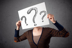 Woman holding paper with drawed question marks in front of her h Royalty Free Stock Photography