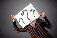 Woman holding paper with drawed question marks in front of her h Stock Photos