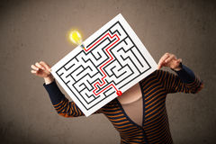 Woman holding a paper with a labyrinth on it in front of her hea Stock Photo