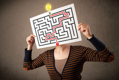 Woman holding a paper with a labyrinth on it in front of her hea Royalty Free Stock Images