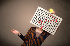 Woman holding a paper with a labyrinth on it in front of her hea Stock Images
