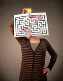 Woman holding a paper with a labyrinth on it in front of her hea Royalty Free Stock Photo