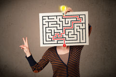 Woman holding a paper with a labyrinth on it in front of her hea Stock Photos