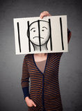 Woman holding a paper with a prisoner behind the bars on it in f royalty free stock image