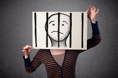 Woman holding a paper with a prisoner behind the bars on it in f Stock Photography