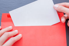 Woman holding paper sheet sticking out of envelope Royalty Free Stock Photography