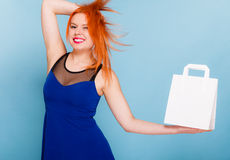 Woman holding paper shopping bag with copy space. Female client customer red hair woman presenting white paper shopping bag with copy space for text,. Retail Stock Photography