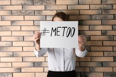 Woman holding paper with text. ` METOO` near brick wall. Problem of sexual harassment at work royalty free stock photos