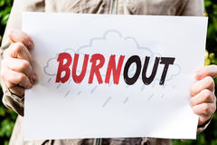 Woman is holding a paper with word burnout Royalty Free Stock Photos