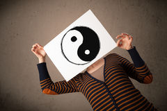 Woman holding a paper with a yin-yang on it in front of her head Royalty Free Stock Photo